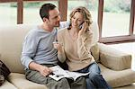 Couple looking at brochure on sofa Stock Photo - Premium Royalty-Freenull, Code: 6114-06603962
