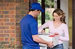 Woman getting a parcel from delivery man Stock Photo - Premium Royalty-Free, Artist: Blend Images, Code: 6114-06604010