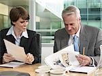 Businesswoman and businessman looking at paperwork Stock Photo - Premium Royalty-Free, Artist: Siephoto, Code: 6114-06604269