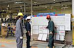 Three factory workers standing near message board Stock Photo - Premium Royalty-Free, Artist: AWL Images, Code: 6114-06604489