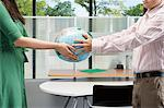 Colleagues holding a globe Stock Photo - Premium Royalty-Free, Artist: Uwe Umsttter, Code: 6114-06604609
