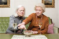 Woman stopping friend from eating a chocolate Stock Photo - Premium Royalty-Freenull, Code: 6114-06604845