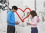 Teenage couple sending text messages Stock Photo - Premium Royalty-Free, Artist: Uwe Umstätter, Code: 6114-06605233