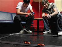 race track (people) - Two friends playing with a toy race track Stock Photo - Premium Royalty-Freenull, Code: 6114-06605245