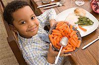 Boy holding bowl of carrots Stock Photo - Premium Royalty-Freenull, Code: 6114-06605762