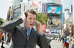 Businessman trying to listen to cell phone Stock Photo - Premium Royalty-Free, Artist: Aflo Relax, Code: 6114-06605912