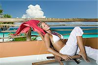 exotic outdoors - Woman relaxing by beach paradise Stock Photo - Premium Royalty-Freenull, Code: 6114-06606047