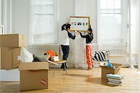 Couple hanging a picture in new apartment Stock Photo - Premium Royalty-Freenull, Code: 6114-06606139