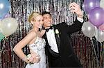 Teenage boy and girl taking a picture at prom Stock Photo - Premium Royalty-Free, Artist: Raymond Forbes, Code: 6114-06606169