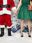 Santa holding hands with a woman Stock Photo - Premium Royalty-Free, Artist: Blend Images, Code: 6114-06606236