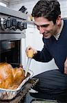 Man basting turkey Stock Photo - Premium Royalty-Free, Artist: Blend Images, Code: 6114-06606398