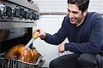 Man basting turkey Stock Photo - Premium Royalty-Free, Artist: CulturaRM, Code: 6114-06606418