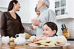 Girl and family in kitchen Stock Photo - Premium Royalty-Free, Artist: Blend Images, Code: 6114-06606437