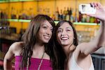 Young women taking picture in a bar Stock Photo - Premium Royalty-Free, Artist: Blend Images, Code: 6114-06606790