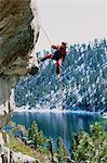 A climber hanging off a rock above a lake Stock Photo - Premium Royalty-Free, Artist: ableimages, Code: 6114-06606840
