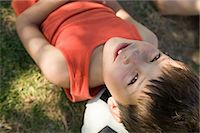 Boy lying on a football Stock Photo - Premium Royalty-Freenull, Code: 6114-06607206
