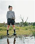 Boy standing at the edge of a pond Stock Photo - Premium Royalty-Free, Artist: CulturaRM, Code: 6114-06607725