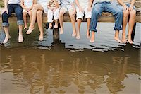 People dangling their feet off a pier Stock Photo - Premium Royalty-Freenull, Code: 6114-06607773