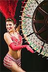 Showgirl spinning the wheel of fortune Stock Photo - Premium Royalty-Free, Artist: Ikon Images, Code: 6114-06607814