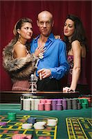 Wealthy man at roulette table with two women Stock Photo - Premium Royalty-Freenull, Code: 6114-06607845