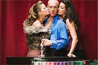 Women kissing man at roulette table Stock Photo - Premium Royalty-Freenull, Code: 6114-06607861