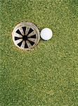 Golf ball on edge of hole Stock Photo - Premium Royalty-Free, Artist: Norbert Schäfer, Code: 6114-06607919