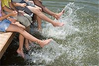 Family splashing water with feet Stock Photo - Premium Royalty-Freenull, Code: 6114-06608446