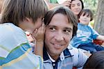 Boy whispering to man Stock Photo - Premium Royalty-Free, Artist: Blend Images, Code: 6114-06608468