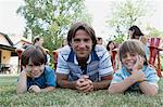 Dad and boys lying on grass Stock Photo - Premium Royalty-Free, Artist: GreatStock, Code: 6114-06608469