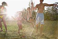 Family playing in sprinkler Stock Photo - Premium Royalty-Freenull, Code: 6114-06608532