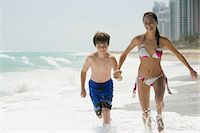 Brother and sister running in the sea Stock Photo - Premium Royalty-Freenull, Code: 6114-06608699