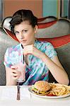 Woman dinning at fast food restaurant Stock Photo - Premium Royalty-Free, Artist: Photocuisine, Code: 6114-06608755