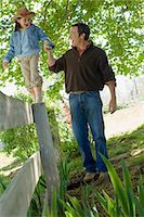 dependable - Girl walking wooden fence, holding fathers hand Stock Photo - Premium Royalty-Freenull, Code: 6114-06608834
