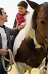 Father assisting son horseback riding Stock Photo - Premium Royalty-Free, Artist: Blend Images, Code: 6114-06608836