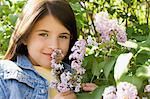 Girl smelling lilac blossoms Stock Photo - Premium Royalty-Free, Artist: Blend Images, Code: 6114-06608861