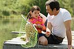 Father and daughter sitting on jetty, holding fishing net Stock Photo - Premium Royalty-Free, Artist: CulturaRM, Code: 6114-06608862