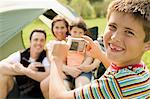 Boy taking photo of family sitting in front of tent Stock Photo - Premium Royalty-Freenull, Code: 6114-06608865