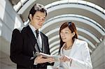 Colleagues looking at organiser Stock Photo - Premium Royalty-Free, Artist: Ikon Images, Code: 6114-06608903