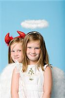 Twin girls dressed as an angel and devil Stock Photo - Premium Royalty-Freenull, Code: 6114-06608978