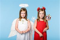 Twin girls dressed as an angel and devil Stock Photo - Premium Royalty-Freenull, Code: 6114-06608989