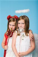 Twin girls dressed as an angel and devil Stock Photo - Premium Royalty-Freenull, Code: 6114-06609005