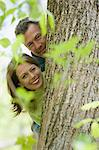 Mature couple standing behind a tree Stock Photo - Premium Royalty-Free, Artist: Robert Harding Images, Code: 6114-06609082