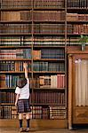 Girl in a library Stock Photo - Premium Royalty-Free, Artist: Westend61, Code: 6114-06609202