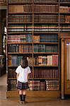 Girl in a library Stock Photo - Premium Royalty-Free, Artist: Westend61, Code: 6114-06609238