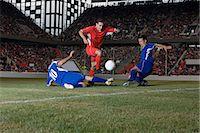 footballeur - Opposite players tackling footballer Stock Photo - Premium Royalty-Freenull, Code: 6114-06609911