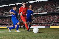 soccer player (male) - Opposite players tackling footballer Stock Photo - Premium Royalty-Freenull, Code: 6114-06609937