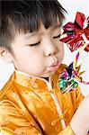 Boy blowing on pinwheel Stock Photo - Premium Royalty-Free, Artist: CulturaRM, Code: 6114-06610034