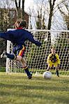 Boy kicking football Stock Photo - Premium Royalty-Free, Artist: CulturaRM, Code: 6114-06610048