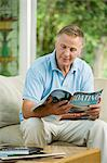 Man looking at boating magazine Stock Photo - Premium Royalty-Freenull, Code: 6114-06610200
