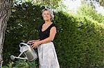 Woman watering garden Stock Photo - Premium Royalty-Free, Artist: Blend Images, Code: 6114-06610298
